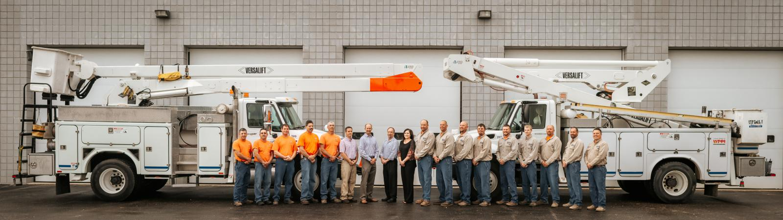 Hartford utilities staff standing in front of two bucket trucks